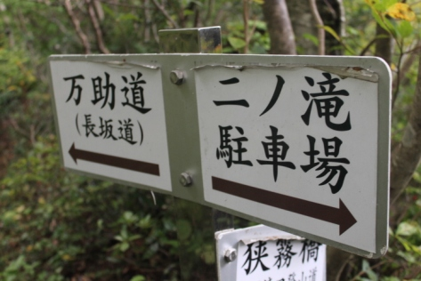 A marker for the Mansuke trail, which is pointing to the left.
