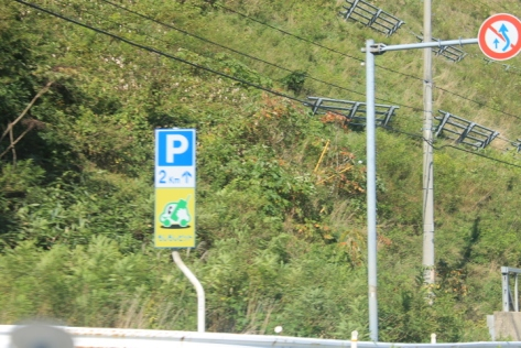 In Japan, it's illegal to use your cell phone while driving. The もしもしピント sign marks spots where you can pull over to use it. Naturally, the car on the sign is both freaking adorable and anthropomorphized.