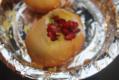 """Pani puri is usually savory and chickpeas are the main flavor profile, but this was a sweet variation. Yogurt, mint (I think), dried chickpeas are mixed together to fill a hollow semolina puff that's about the size of an egg. Pomegranate seeds are sprinkled on top. As Vibhor handed this to me, he instructed me, """"You have to take this like a shot, okay? All at once."""" That made me a bit nervous, but the way these flavors collided in my mouth - the sweetness of the pomegranate, the slightly sour tanginess of the yogurt, the crispness of the semolina - made it clear that you have to taste everything all at once for the full flavor bombshell. I couldn't help but crow in delight after eating this."""