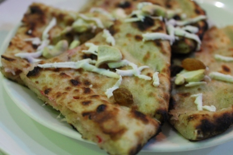 Kabuli naan, stuffed with cherries and coconut and topped with cashews, dates, and shredded paneer.