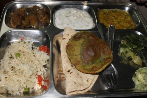 Another thali, this one eaten at a home cooking demo in Orchha. Counterclockwise from foreground left: pulao, chapati, fenugreek poori, fresh guava chutney, aloo saag (spinach and potatoes), dal fry, poori raita, and aubergine curry.