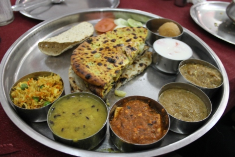 The thali I ate in Varanasi. Counterclockwise from foreground left: pulao (like Indian fried rice), dal fry, paneer masala curry, vegetable kofta, cashew curry, tomato raita, gulab jamun, fresh vegetables, and papad. Stacked in the middle is butter naan and stuffed paratha.