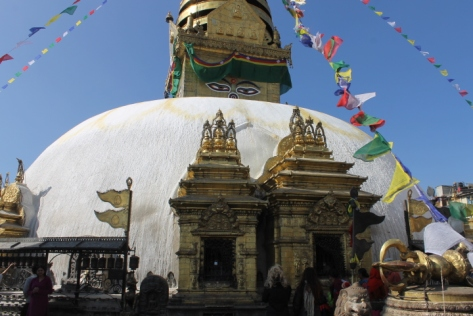 There's a vast contract between the simple white dome and the intricate golden decorations and small shrines around it.